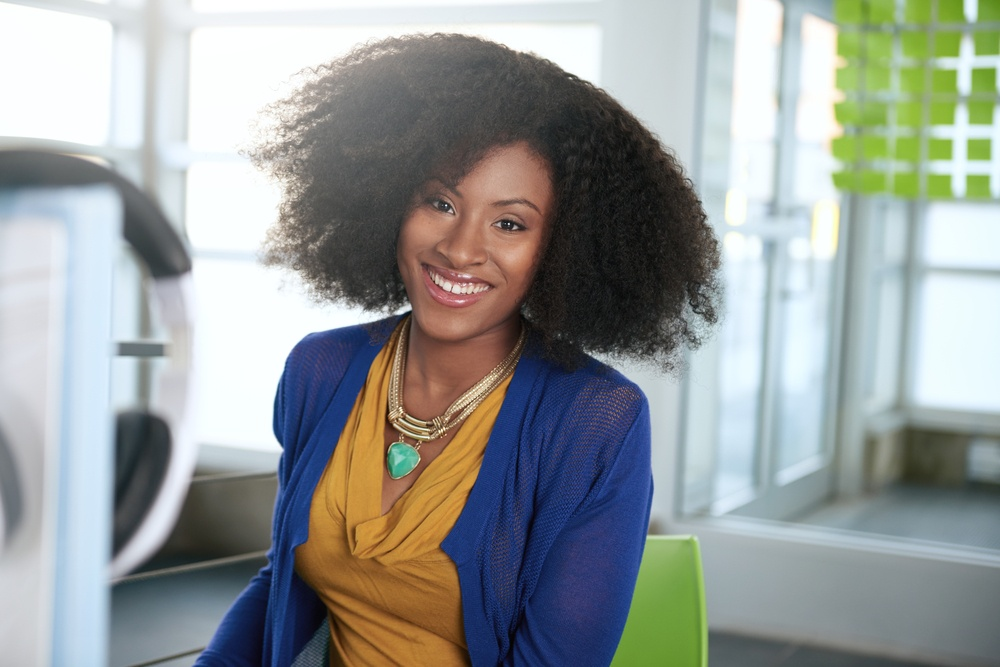 Portrait of a smiling woman with an afro at the computer in bright glass office.jpeg