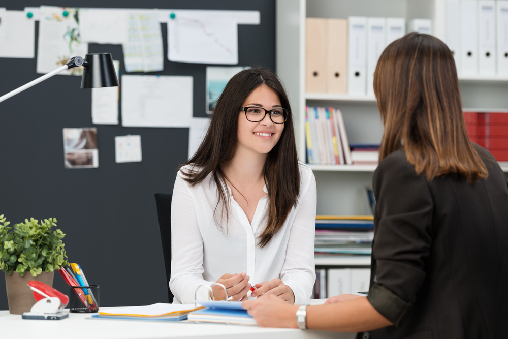 Two young businesswomen having a meeting in the office sitting at a desk having a discussion with focus to a young woman wearing glasses-4