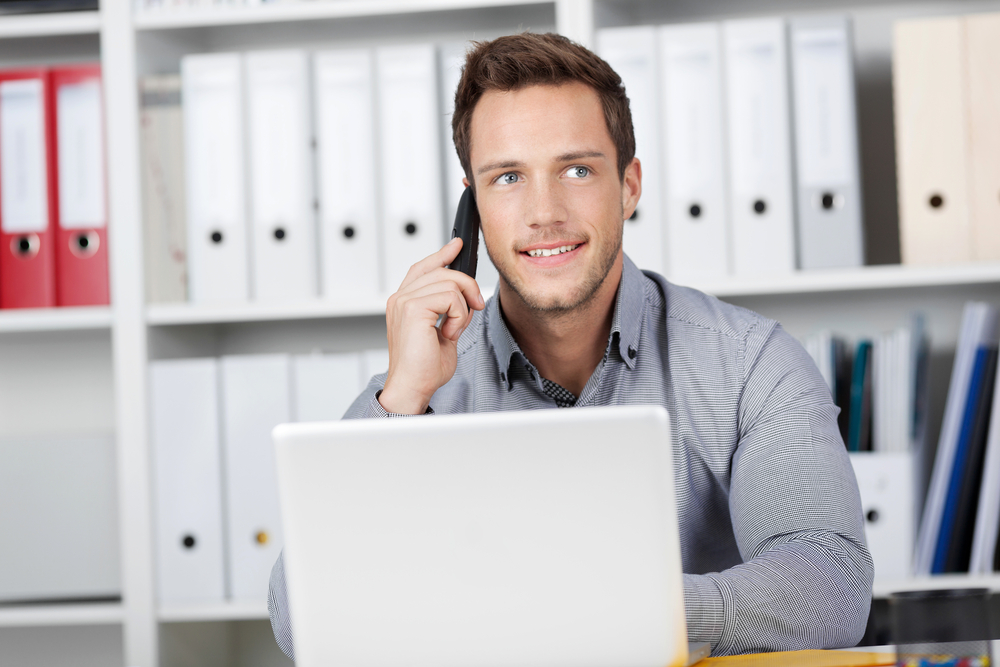 Young smiling businessman on the phone in office